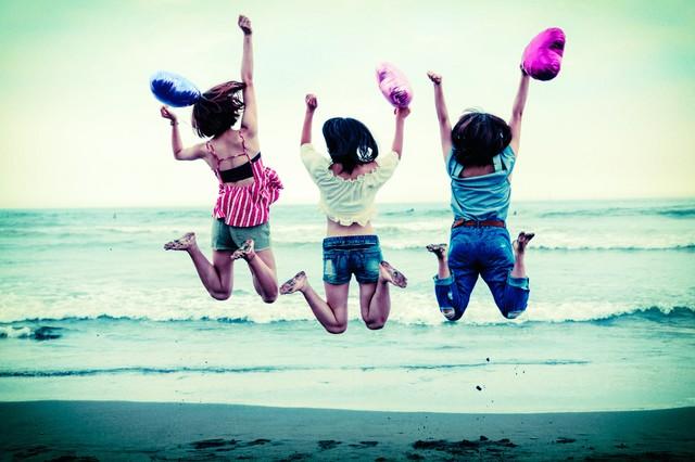 波打ち際でジャンプするハッピーな若い女性三人組