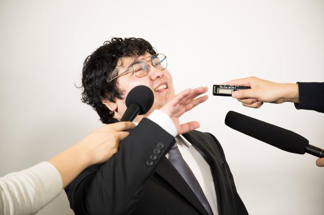 執拗な囲み取材を受ける男性