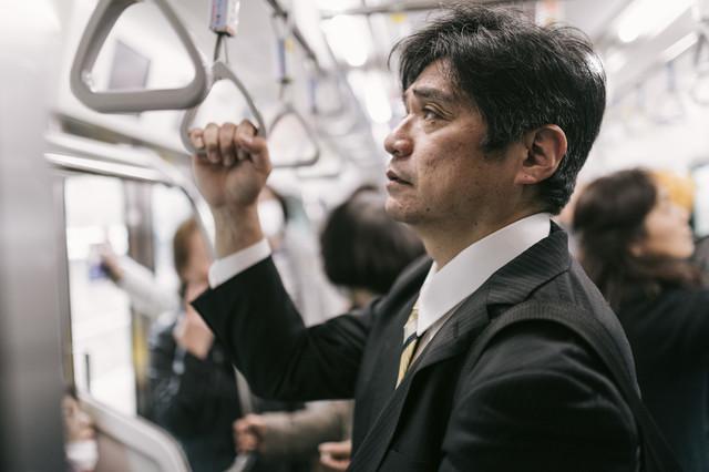 単身赴任で満員電車に揺られて通勤するお父さん