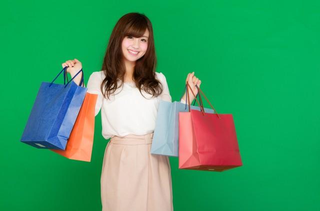 両手いっぱいの買い物袋を持ったセールが大好きな女性(グリーンバック)