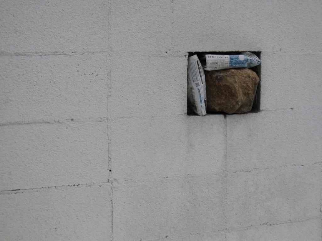 壁の穴を石でふさぐ写真