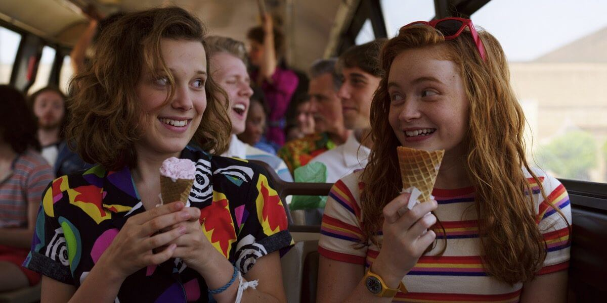 two young ladies who have ice cream are laughing