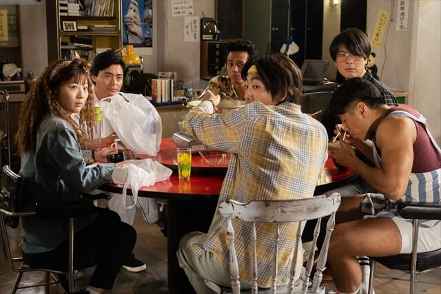 some adult including one lady sitting one big table and easting something from the scene of tv show naked director