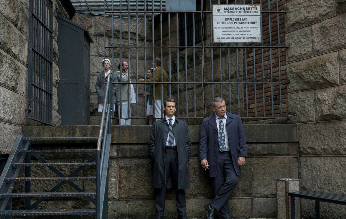 two FBI agent standing in front of bricks building from the scene of tv show mindhunter season 2