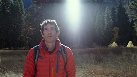 Alex honnold with red jacket looks up from the scene of FreeSolo