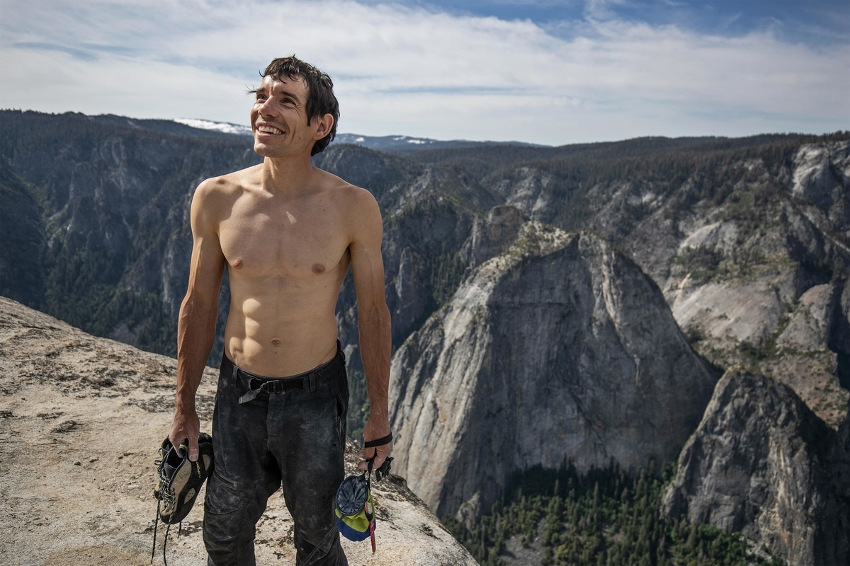 Alex Honnold looks up the sky from the top of mountain from the scene of FreeSolo