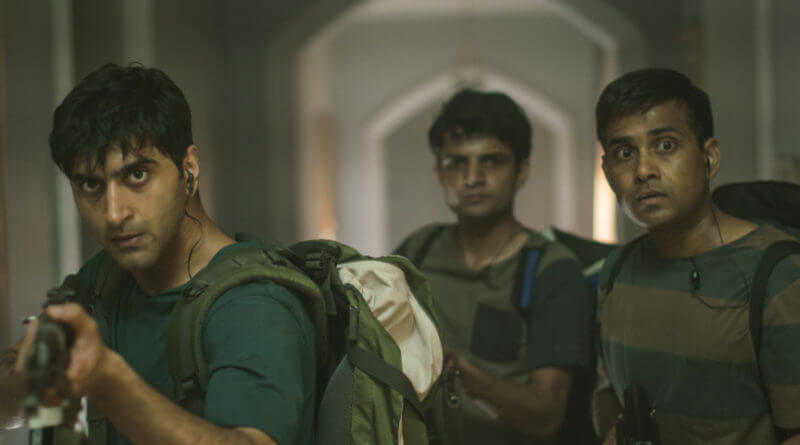 three young Indians with gun sneaking in the hotel from the scene of Hotel Mumbai