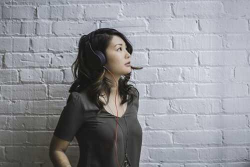 ヘッドフォンで音楽を聴いてる女性