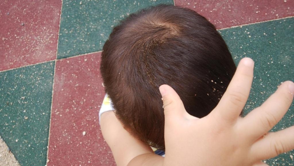 自分で頭に砂をかける幼児