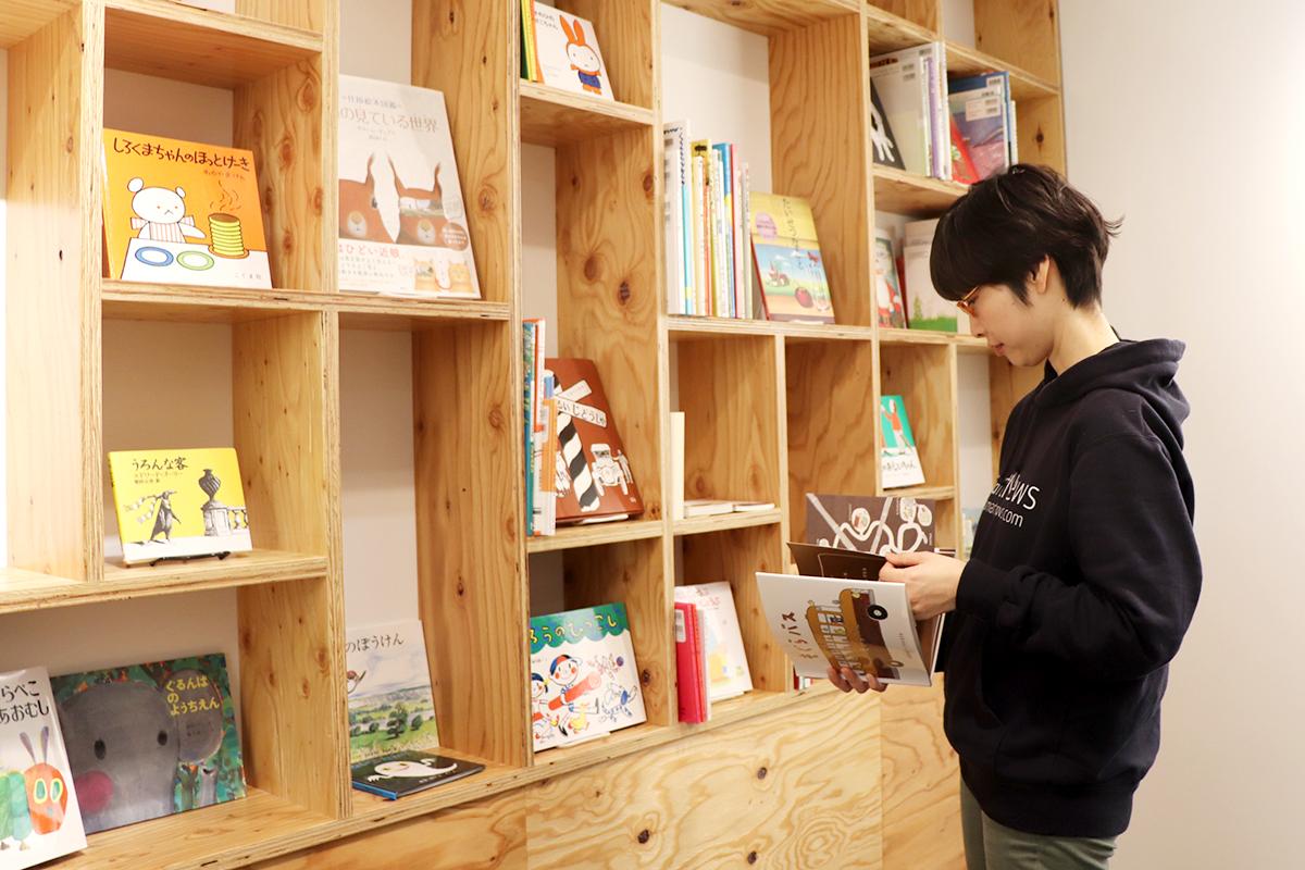 絵本が並ぶ「石井桃子部屋」で本を手に取る青井さん