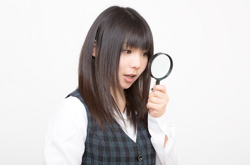 虫眼鏡を見る女性の画像
