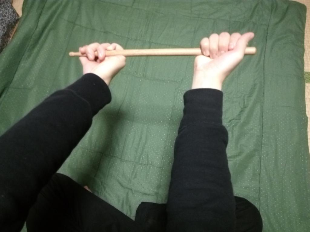 ドラムスティックを持った手の片手をひねる
