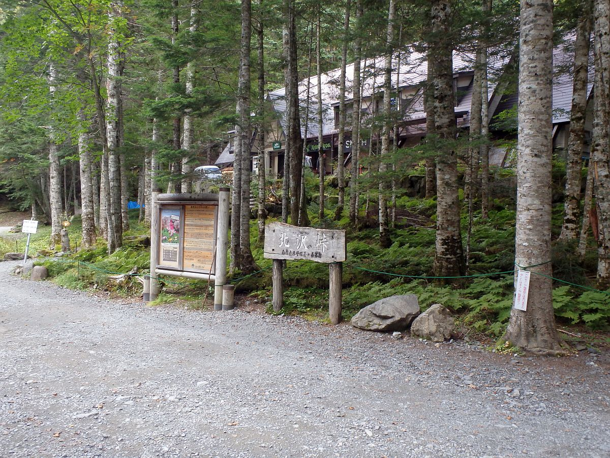 山梨側より撮影した北沢峠の看板。後方の山小屋はこもれび山荘(旧長衛荘)