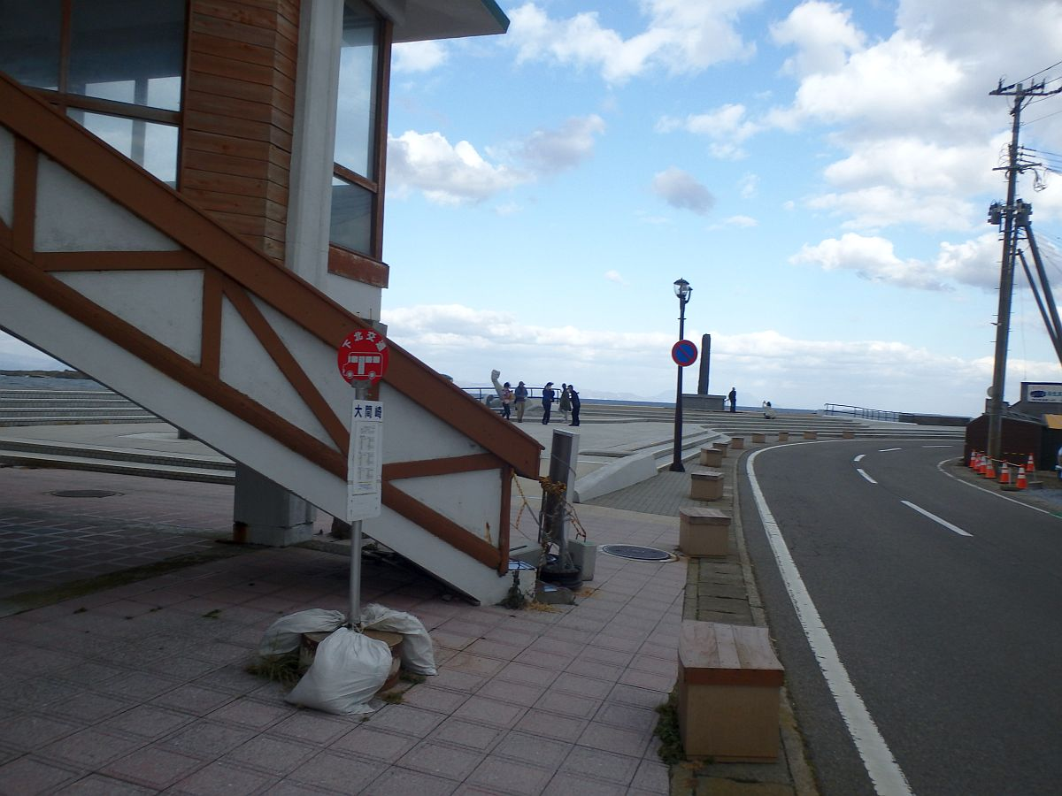 バス停の奥で強風に縮こまる観光客