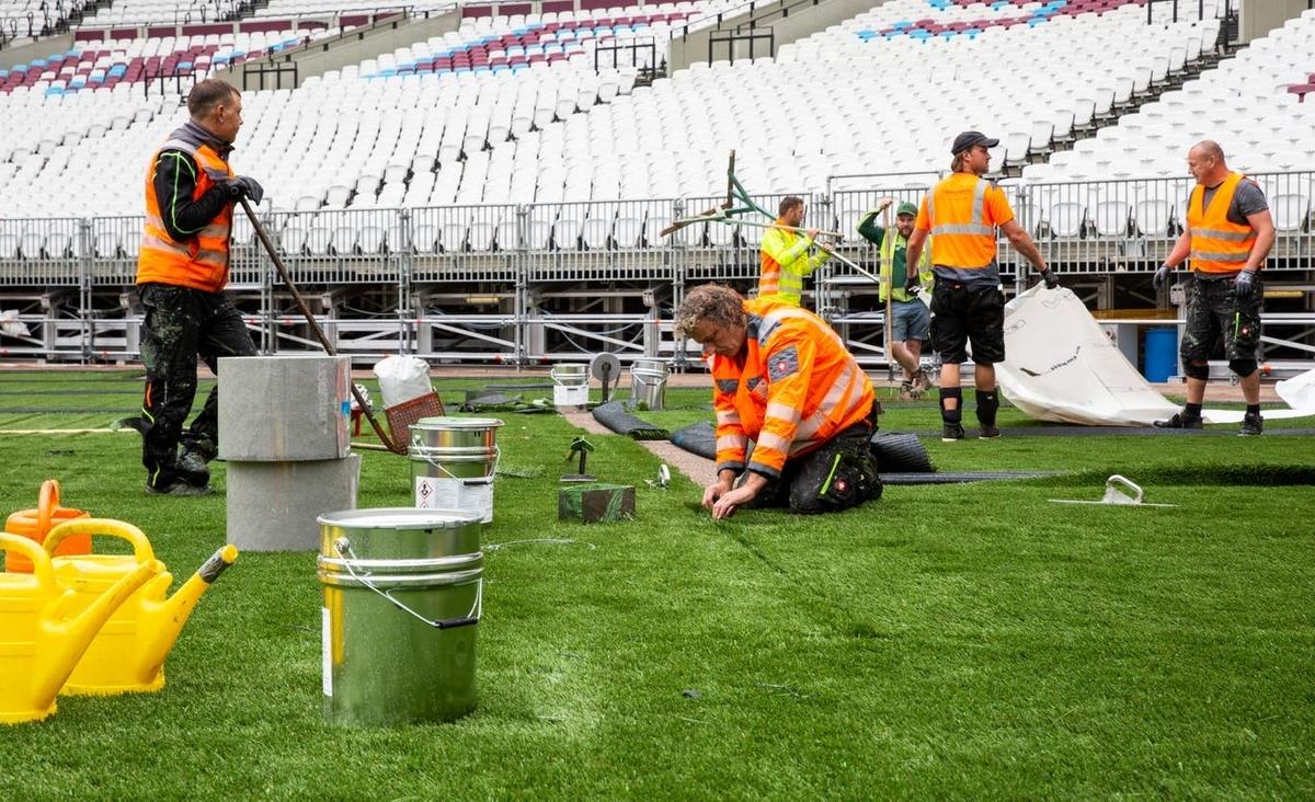 画像:人工芝を敷設する作業員