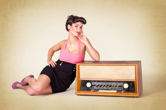 Pinup Mädchen liegt neben altem Radio