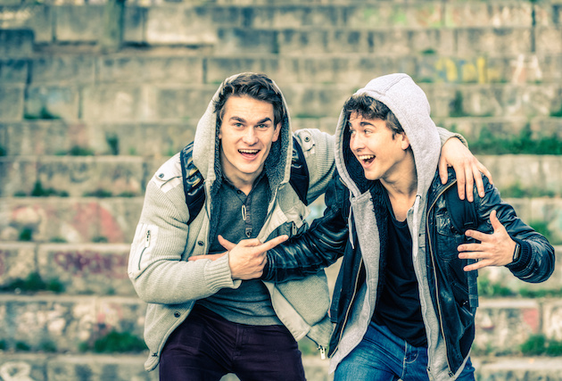 Young hipster brothers having fun with each other - Best friends sharing free time together in urban area outdoors - Handsome guys with winter fashion clothes enjoying everyday life moments