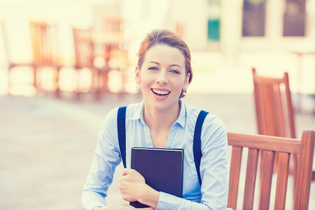 Laughing young woman with book