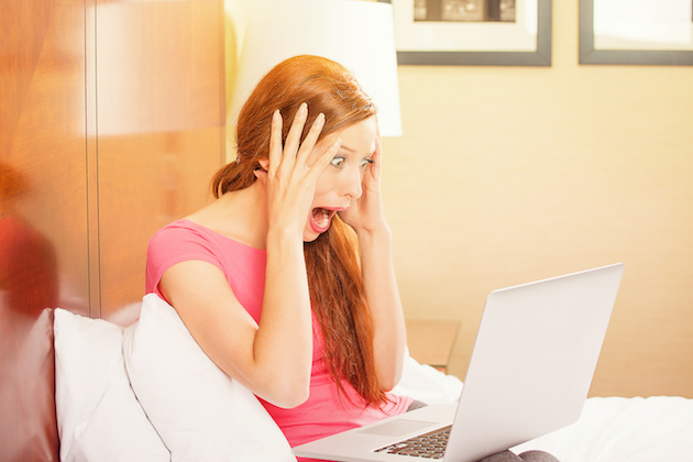 Shocked funny casual young woman using laptop
