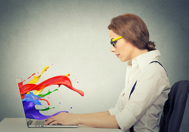 woman working on computer colorful splashes coming out of screen