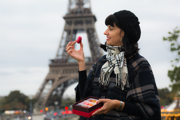 Young caucasian woman holding a french macaroons
