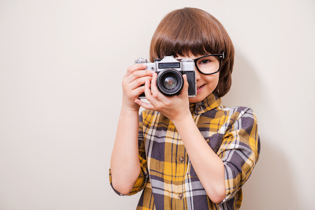He is fond of shooting. Little boy in eyewear holding camera and smiling while standing against grey background