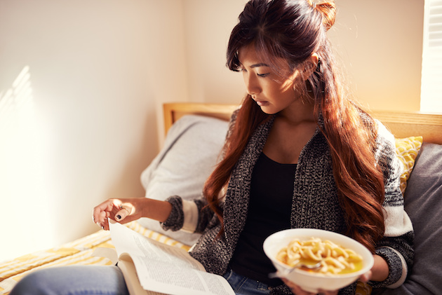 asian girl reading book and eating chicken soup in bed