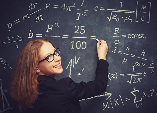 happy girl student, the teacher writes on blackboard chalk formula