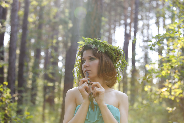 Beautiful model in a forest with a vintage key