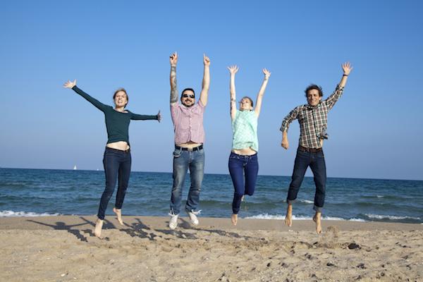 Amigos saltando sobre la arena de la playa