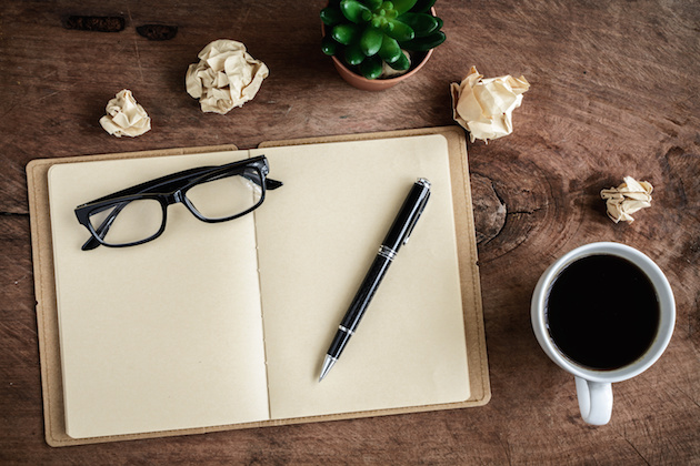 Cup of coffee with notebook on old wooden desk