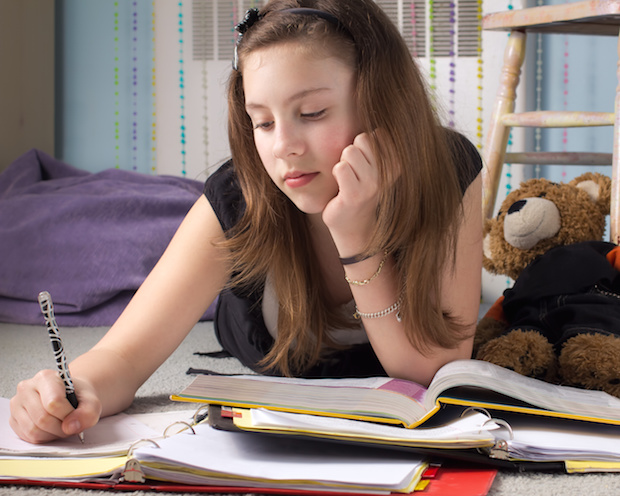 Cute young teenage girl doing homework in her bedroom