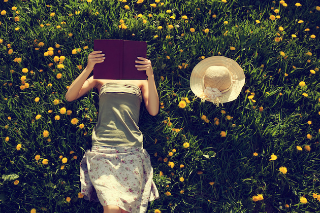 Girl lying in grass, reading a book.