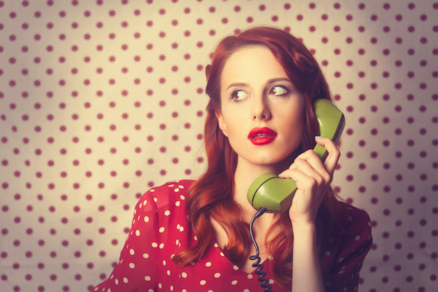 Portrait of a redhead girl with green dial phone