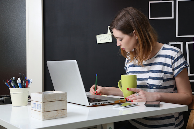 Young woman in front of laptop writing a note