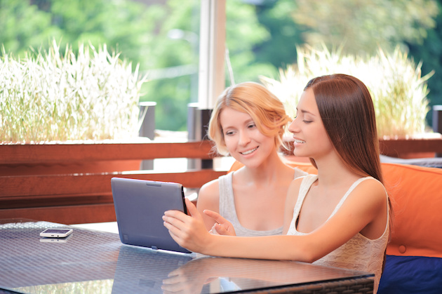 Pair of girlfriends in cafe with tablet