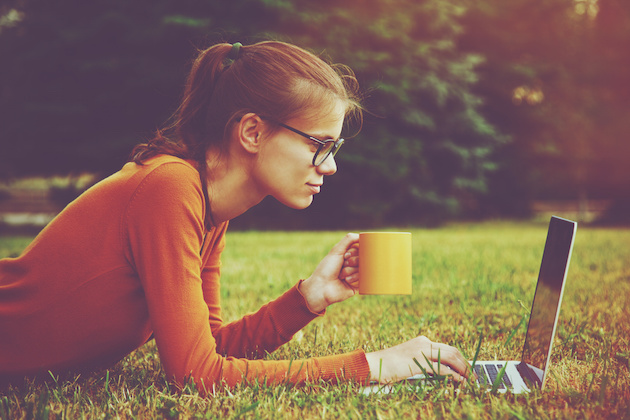 girl lying on the grass and using laptop and typing with coffee or tea mug