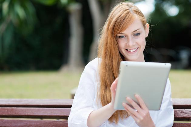 frau sitzt im park und liest am tablet-pc