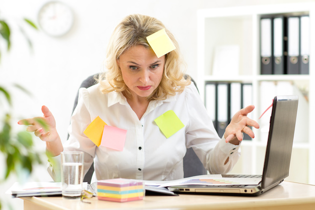 Funny overworked businesswoman working in office and looking at stickers reminder notes