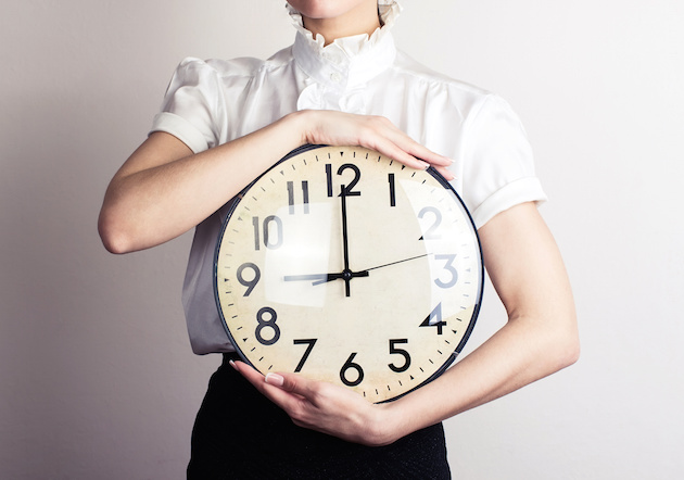 Business woman holding a clock