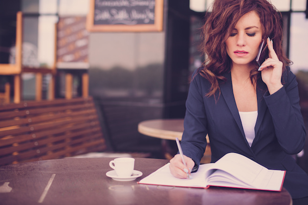 Young business woman sitting at the table, writing in a notebook and talking on the phone. On table she has cup of coffee