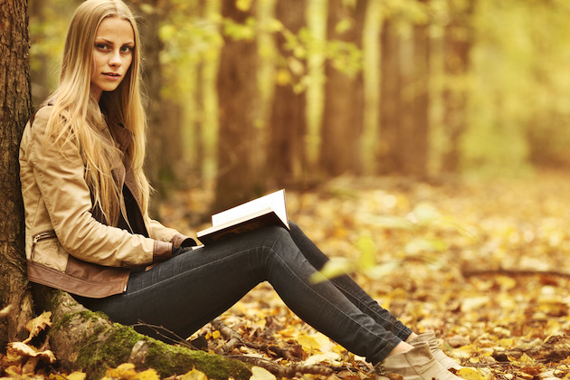 young beautiful girl with a book in the autumn forest