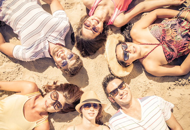 group of friends lying on the beach