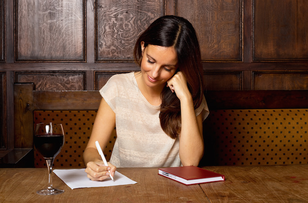 young woman writing with a glass of wine.