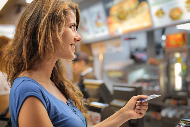 Young woman paying at a fast food restaurant