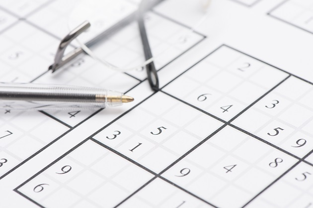 Sudoku puzzle, pen and glasses
