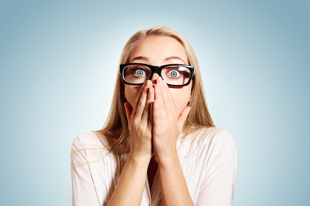 Closeup portrait of surprised young handsome blonde business woman looking shocked in full disbelief hands on mouth open eyes with glasses, isolated on blue background. Positive human emotion facial