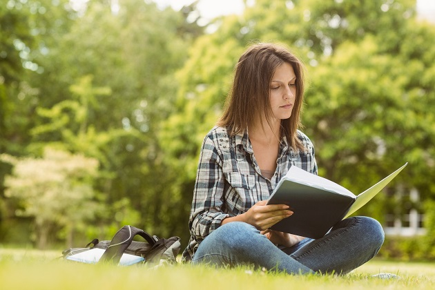University student sitting reading book