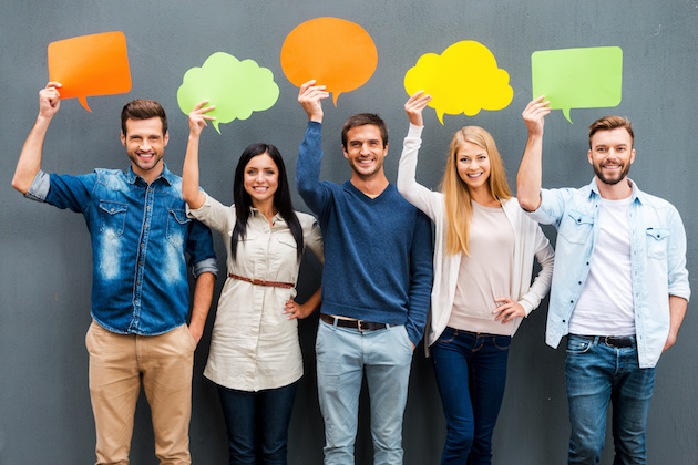 Global communications. Group of happy young people holding empty speech bubbles and looking at camera while standing against grey background