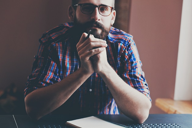 handsome bearded man with pen and notebook